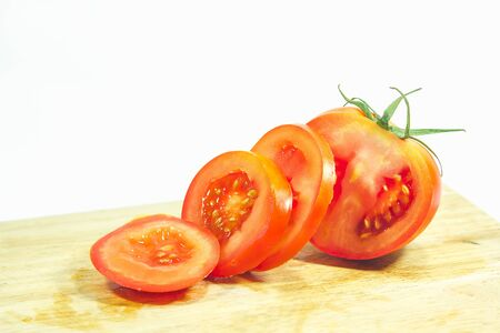 Red tomatoes on wood, red tomatoes being cut. Tomatoes are eaten when ripe, ripe, red Or fully ripe orange