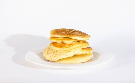 pancakes are stacked on a white plate. On a white background Stock Photo