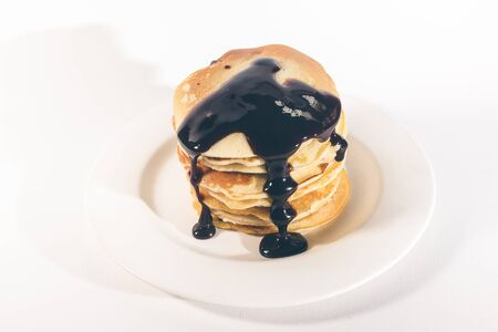 pancakes, stacked on a white plate, are topped with chocolate. 写真素材