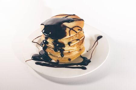 pancakes, stacked on a white plate, are topped with chocolate. Banco de Imagens