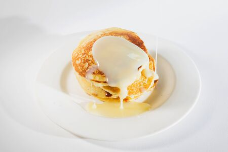 pancakes stacked on a white plate, Pancakes are topped with sweetened condensed milk. 写真素材