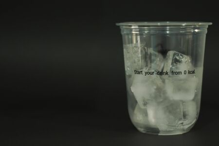 Ice cubes in plastic glasses on a black background