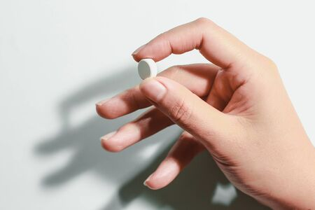 Medication on hand,White seed medicine on fingers, on a blue background