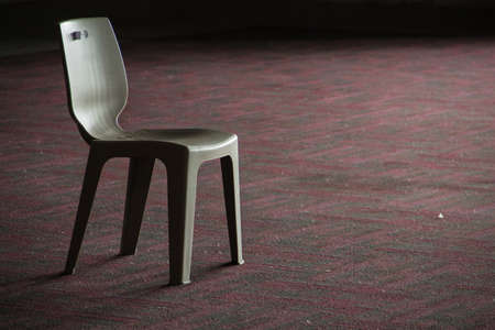 One gray chair placed on the red carpet area.. Stockfoto