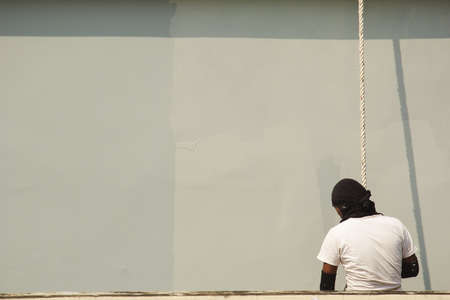 A male worker is painting a tall building abseiling.