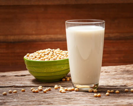 Soybeans and soy milk in a glass on wood background.