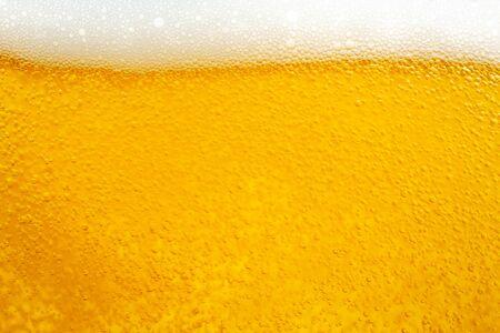 Verter cerveza con espuma de burbujas en vidrio para fondo y diseño.