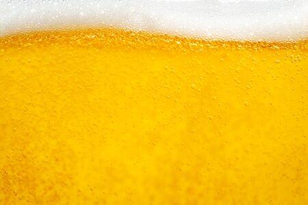 Verter cerveza con espuma de burbujas en vidrio para fondo y diseño. Foto de archivo