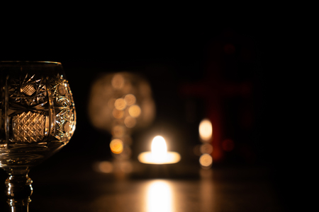 Crystal Brandy Glass on the dark background with candle.