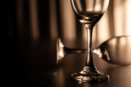 Two wine glasse, one overturn. Imagens