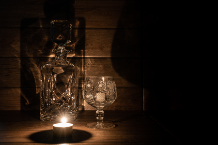 Brandy glass and bottle and candle