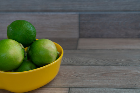 Limes in the yellow bowl on the table. Stock Photo - 116986825