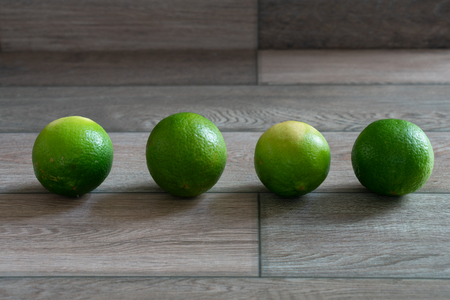 Limes arrange on the wooden background. Stock Photo - 116986826