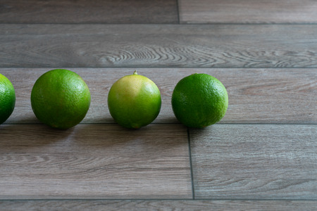 Limes arrange on the wooden background.