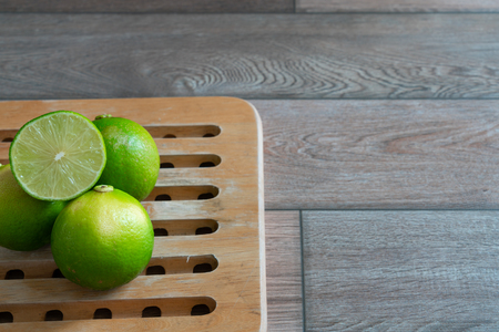 Limes on a wooden tray in the kitchen.
