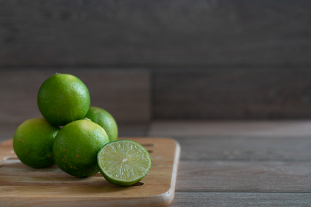 Group of limes on wooden tray on the table. Stock Photo - 116986860