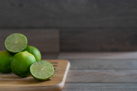 Group of limes on wooden tray on the table. Stock Photo