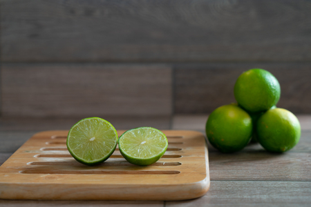 Cut limes on wooden tray prepare for cooking.