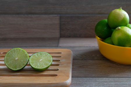 Cut limes on wooden tray prepare for cooking. Stock Photo - 116986865