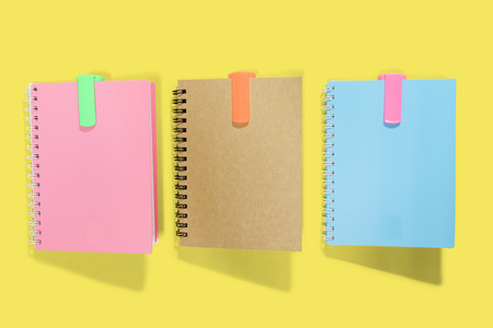 Photo of Three note book, blue pink and brown paper cover on yellow screen