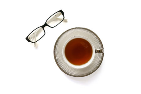 Photo of Eye glasses and a cup of tea on white background