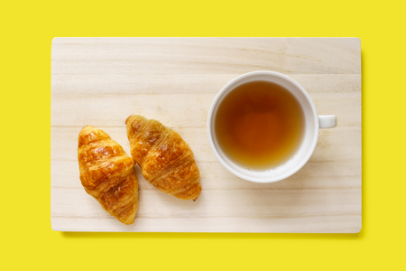 Two croissants and a cup of tea on a wooden tray isolated on yellow background