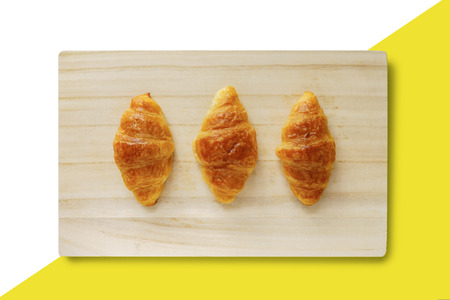 Three croissants on a wooden tray isolated on yellow and white background