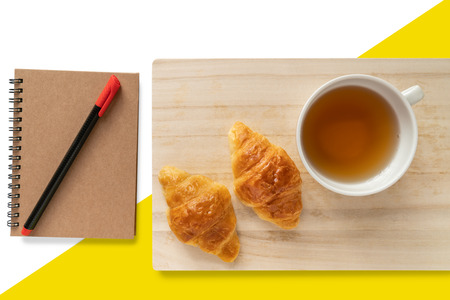 Two croissants and a cup of tea on a wooden tray isolated on white and yellow background Banco de Imagens