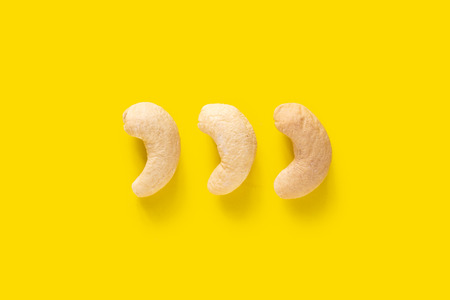 Three cashew nuts isolated on yellow background