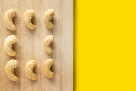Cashew nut on wooden tray on yellow background