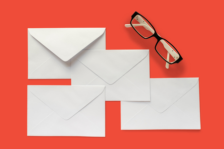 Four letter envelopes and eye glasses isolated on red background