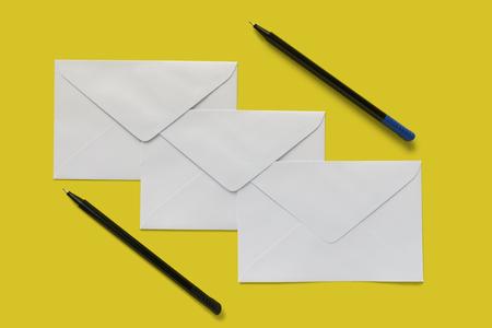 Enveloppe de lettre blanche et stylos isolés sur fond jaune