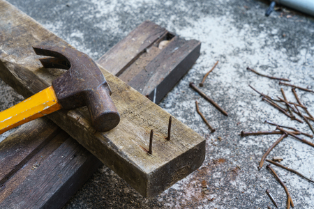 Photo of Hammer, rusty nail and wood for carpenters job