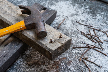 Photo of Hammer, rusty nail and wood for carpenter's job