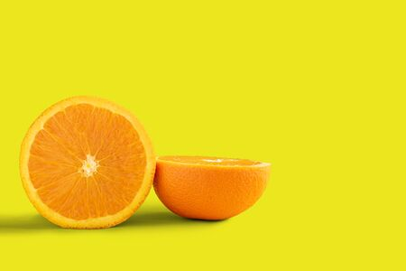 Half cut Navel orange isolated on yellow background