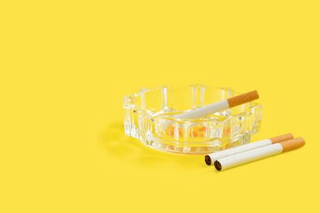 Photo of cigarette and ashtray on yellow background