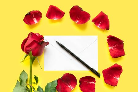 A single red rose, rose petals, a pen and a letter envelope isolated on yellow background Фото со стока
