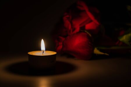 tealight candle and red rose at midnight time