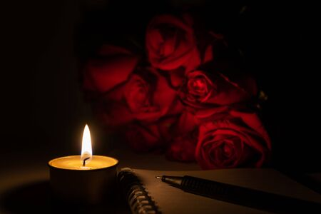 Tealight candle, pen, note book and roses at midnight time Imagens