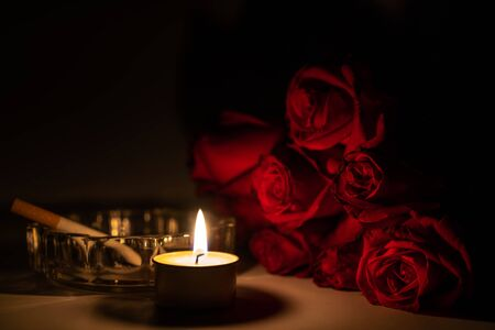 Tealight candle, red roses, cigarette and ashtray at midnight time Imagens - 132040825