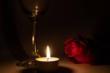 Tealight candle, wine glass and rose in the dark night