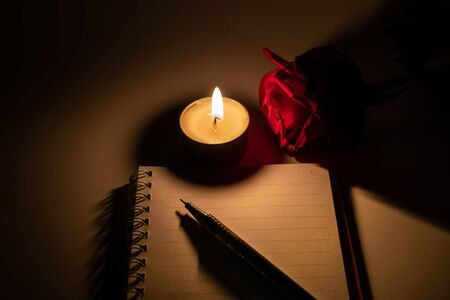 Tealight candle, pen, note book and roses at midnight time Imagens - 132040305