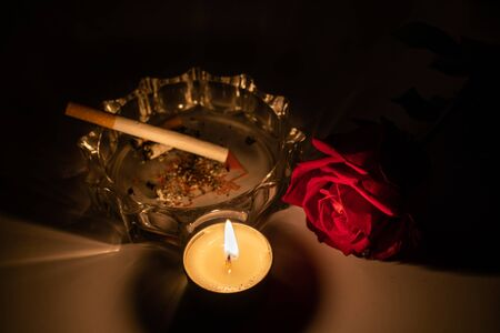Tealight candle, red roses, cigarette and ashtray at midnight time