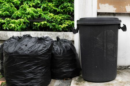 A black plastic bin and black plastic garbage bags placed in front of the house waiting for the garbage collection truck. Reklamní fotografie
