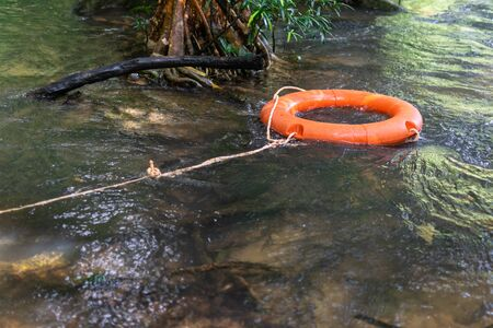 A orange lifebuoy at the waterfall