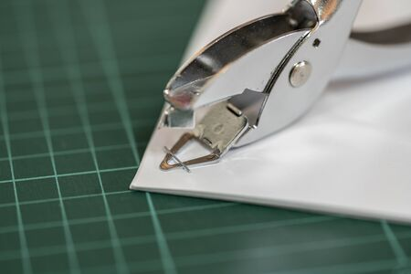 The staple remover is removing the staple from the stapled document.