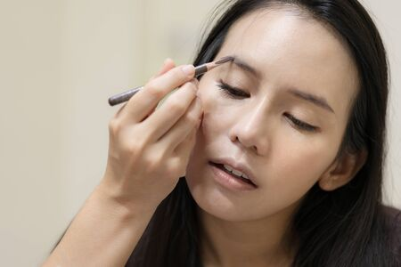 A asian woman is using eyebrow pencil to draw on eyebrows