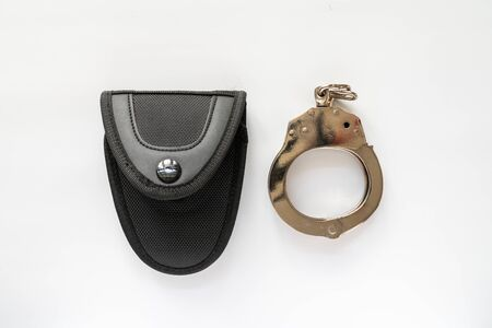 Handcuff and bag isolated on white background