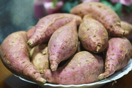 A pile of sweet potato in a white bowl on a wooden table