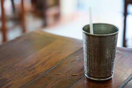 The white drinking straw in a metal glass that has cold water until steam condenses on the side of the glass.